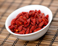 Dehydrated goji berries in bowl on mat Stock Photo