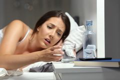 Dehydrated woman reaching a glass of water. On the bed in the night at home stock images