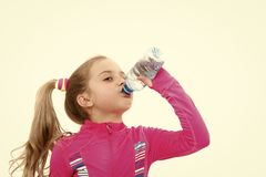 Dehydration, thirst concept. Child feel thirsty in pink suit isolated on white. Girl drink water from bottle. Fluid balance, hydration. Health and healthy royalty free stock photo