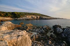Dei Benedettini, la côte rocheuse de la Puglia, Italie, Cala de l'île de domino de San, au coucher du soleil photo libre de droits