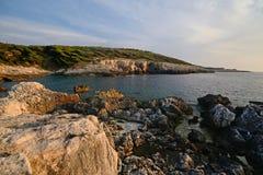 Dei Benedettini, la costa rocosa de Puglia, Italia, Cala de la isla del dominó de San, en la puesta del sol foto de archivo libre de regalías