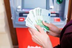 Dei contanti soldi fuori ad un BANCOMAT Immagine Stock