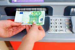 Dei contanti soldi fuori ad un BANCOMAT Fotografie Stock