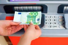 Dei contanti soldi fuori ad un BANCOMAT Fotografie Stock Libere da Diritti