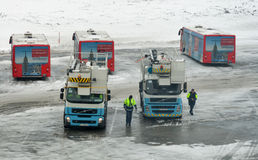 Deicing cars and passenger buses in Boryspil Airport. Kiev, Ukraine. Workers with deicing service cars and passenger buses in winter Boryspil International Stock Image
