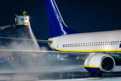 Deicing passenger airplane during heavy snow Stock Photo