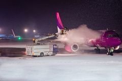 Deicing passenger airplane during heavy snow. At night Royalty Free Stock Images