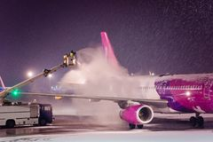 Deicing passenger airplane during heavy snow. At night Stock Image