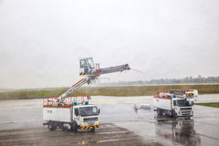 Deicing truck deices a plane before. MUNICH, GERMANY - OCTOBER 17: Deicing of a plane before take off on October 27,2012 in Munich, Germany. The deicing applied Stock Photos