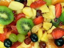 Deicious fruit salad. Strawberries, kiwi fruits, orange, grapes, cherries, pomegranate, mango, apple and pineapple Stock Images