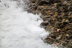 Deixar de funcionar de rolamento acena em seixos em uma praia em Clarence Drive, entre Kleinmond e baía de Gordons, cabo ocidenta imagens de stock