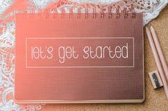 Deje el ` s conseguir el texto comenzado en el cuaderno marrón con la iluminación y el penci Foto de archivo libre de regalías