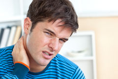 Dejected caucasian man having a neck ache Royalty Free Stock Image