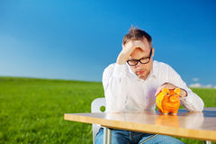Dejected man looking at his piggy bank Stock Photography