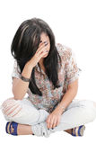 Dejected woman with hands on face sitting on floor Royalty Free Stock Photo