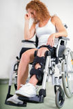 Dejected woman with her knee in a brace Royalty Free Stock Photo