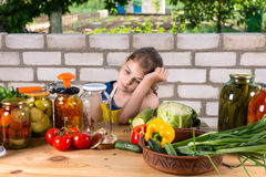 Dejected young girl bottling vegetables Stock Photo
