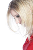 Dejected young woman. Closeup sideways portrait of the head of a dejected young woman looking down with her blonde hair partially obscuring her face Royalty Free Stock Images