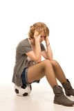 Dejected young woman sitting on a soccerball Stock Image