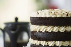 Dekadent chokladlagerkaka med kaffeurnan royaltyfria foton