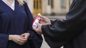 Dekan av fakulteten som uttrycker tacksamhet och räcker diplomet till den kvinnliga studenten stock video