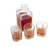 Dekantator i trzy szkła z whisky na lekkim tle Zdjęcie Stock