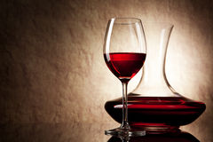 Dekantiergefäß mit Rotwein und Glas auf einem alten Stein Lizenzfreie Stockfotos