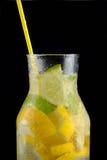 Dekantiergefäß mit Sodawasser, Zitronen und einem Stroh auf einem schwarzen Hintergrund Lizenzfreie Stockfotografie
