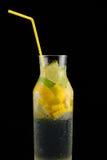 Dekantiergefäß mit Sodawasser, Zitronen und einem Stroh auf einem schwarzen Hintergrund Stockbild