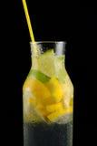 Dekantiergefäß mit Sodawasser, Zitronen und einem Stroh auf einem schwarzen Hintergrund Lizenzfreie Stockfotos