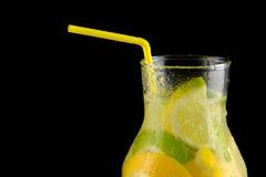 Dekantiergefäß mit Sodawasser, Zitronen und einem Stroh auf einem schwarzen Hintergrund Stockfoto