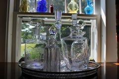 Dekantiergefäße des geschliffenen Glases im Fenster Lizenzfreie Stockfotografie