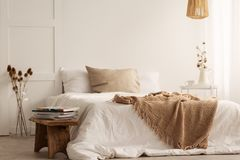 Deken op wit bed in natuurlijk slaapkamerbinnenland met installaties en houten kruk royalty-vrije stock afbeelding