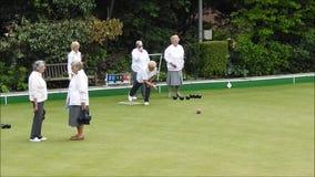 Dekens oap gepensioneerden die kommen spelen die groene in openlucht actieve sporten werpen stock footage
