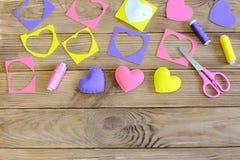 Dekor för hjärtor för dag för valentin` s Färgrika filthjärtor dekor, filtrester, pappers- mall, sax, tråd på den wood tabellen Royaltyfri Fotografi