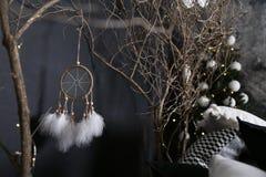 Dekor från träfilialer med ett grönt gran-träd mot bakgrunden av Dreamcatcher med vita fjädrar vit-svart kuddar arkivfoto