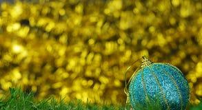 Dekoraci świąteczna błękitna jaskrawa błyszcząca piłka na złotym bokeh plecy Obraz Stock