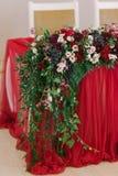Dekoracja ślubny stół nowożeńcy zielenie w kwiatach i Poślubiać w czerwonym kolorze obrazy stock