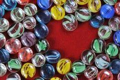 Dekoracja otoczaki drylują serce kształtującego na czerwonym aksamitnym tle Fotografia Stock