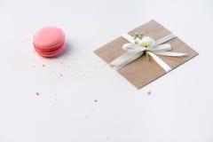 Dekoracyjna Kraft koperta z łęku i menchii macaron odizolowywającym na bielu, ślubny zaproszenie karty pojęcie Obraz Royalty Free