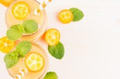 Dekoracyjna rama pomarańczowego cytrusa kumquat owocowy smoothie w szkle zgrzyta z słomą, nowy liść, śliczna dojrzała jagoda, odg Zdjęcie Stock