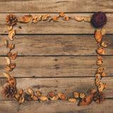 Dekoracyjna rama robić od suchych rożków, kwitnie i ziarna na nieociosanym drewnianym stole Obraz Royalty Free