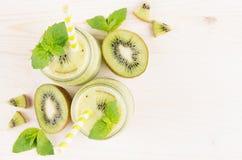 Dekoracyjna rama zielony kiwi owoc smoothie w szkle zgrzyta z słomą, nowy liść, śliczna dojrzała jagoda, odgórny widok Zdjęcia Stock