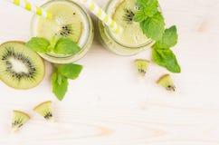 Dekoracyjna rama zielony kiwi owoc smoothie w szkle zgrzyta z słomą, nowy liść, śliczna dojrzała jagoda, odgórny widok Obrazy Stock
