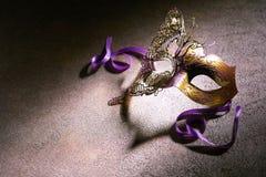Dekoracyjna złocista karnawał maska z purpurowymi faborkami obrazy royalty free