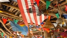 Dekoracyjne flagi państowowe różni kraje wiesza na sznurkach w drewnianym tropikalnym bungalowie Egzotyczny rasta bar