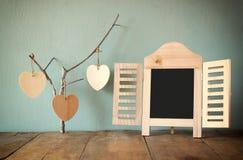 Dekoracyjnego chalkboard ramowi i drewniani wiszący serca nad drewnianym stołem Obrazy Royalty Free