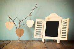 Dekoracyjnego chalkboard ramowi i drewniani wiszący serca nad drewnianym stołem przygotowywający dla teksta lub mockup retro filt Obrazy Royalty Free