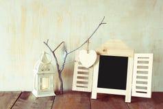 Dekoracyjnego chalkboard ramowi i drewniani wiszący serca nad drewnianym stołem przygotowywający dla teksta lub mockup retro filt Obrazy Stock