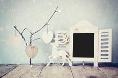 Dekoracyjnego chalkboard ramowi i drewniani wiszący serca nad drewnianym stołem przygotowywający dla teksta lub mockup retro filt Fotografia Stock